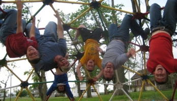 Picture of Roy Moranz with family hanging on jungle gym.